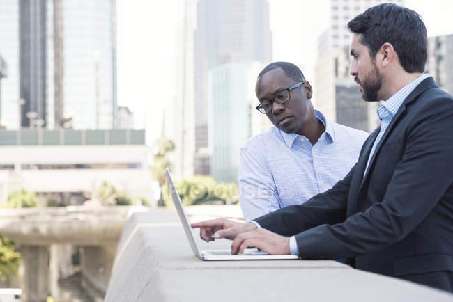 Два бизнесмена используют ноутбук вместе в городе — стоковое фото