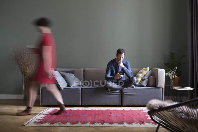 Мужчина сидит на диване в гостиной, в то время как женщина проходит на переднем плане — стоковое фото