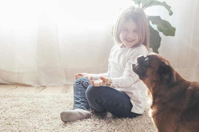 Happy little girl playing with dog at home — Stock Photo