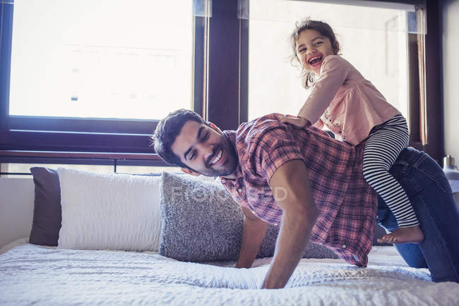 Daughter playing with father riding on his back — Stock Photo