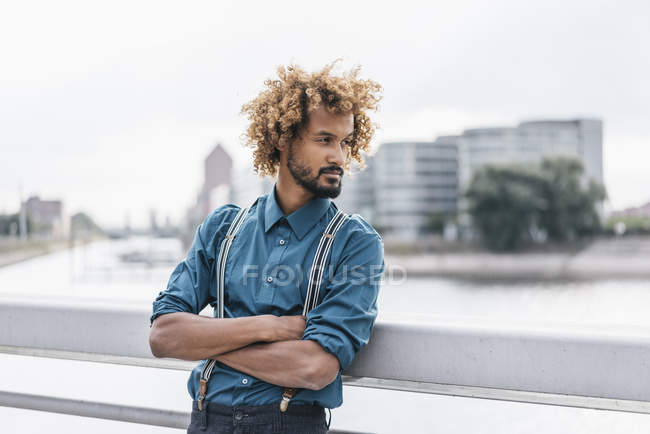 Young man leaning on railing with arms crossed — Stock Photo