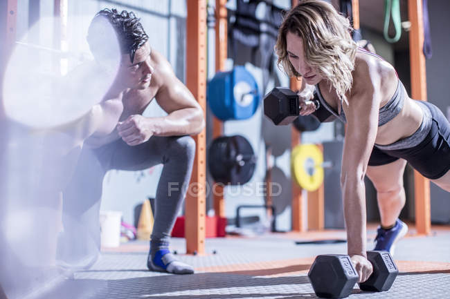 Fitness instructor with woman doing dumbbell press ups in gym — Stock Photo
