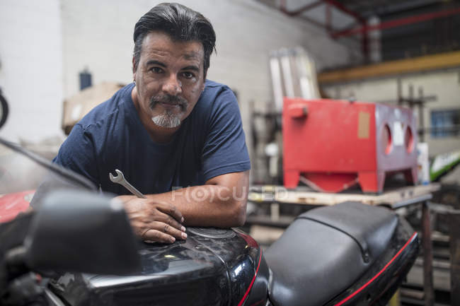 Motorcycle mechanic working in workshop and looking at camera — Stock Photo