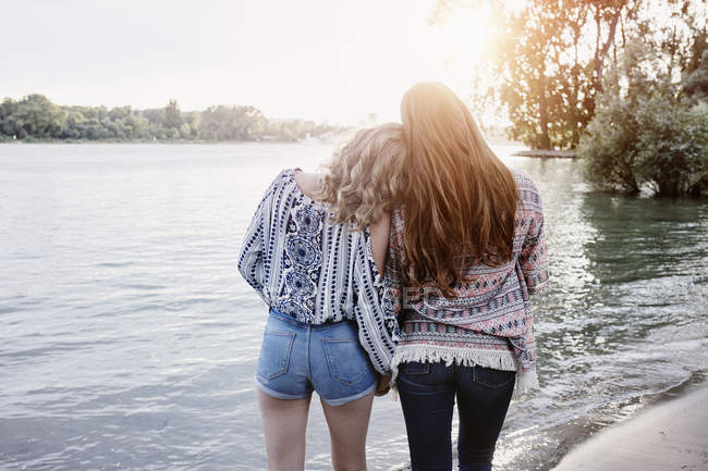 Portrait of two teenage girls standing near river — Stock Photo