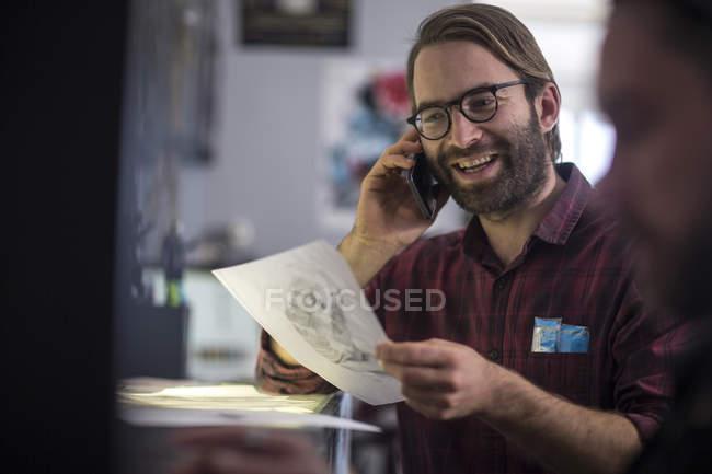 Happy graphic designer talking on the phone — Stock Photo