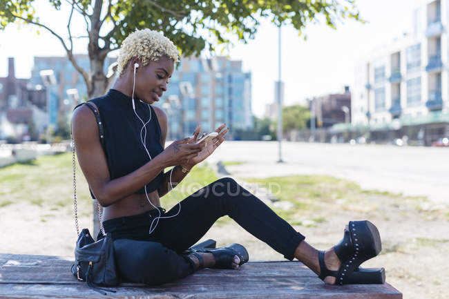 Smiling young african woman with cell phone and earbuds — Stock Photo