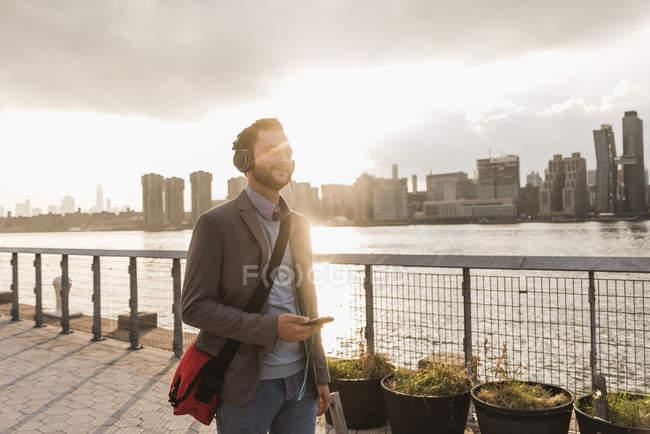 Junger Mann zu Fuß mit Kopfhörer und Handy am East River — Stockfoto