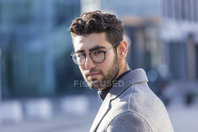 Portrait of young businessman with beard and spectacles looking at camera — Stock Photo