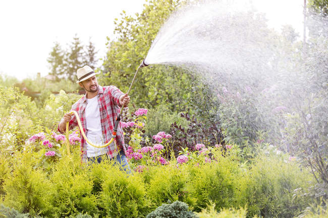 Gardener watering plants in plant nursery — Stock Photo