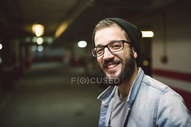 Porträt eines lächelnden lässigen Mannes in einer Garage — Stockfoto