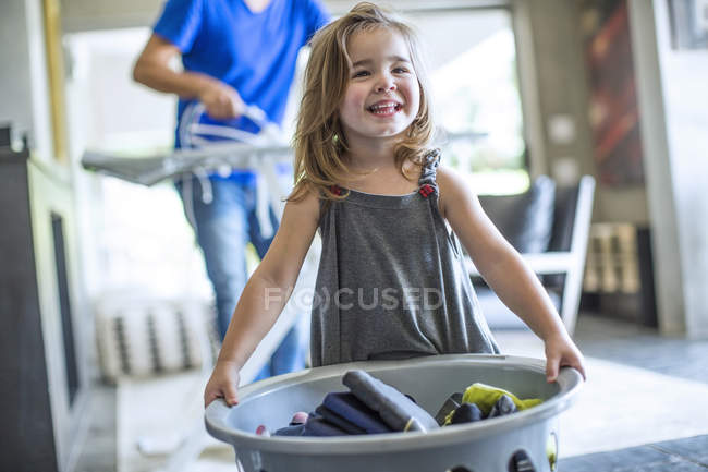 Happy baby girl holding laundry basket,helping with home chores,father ironing at background — Stock Photo