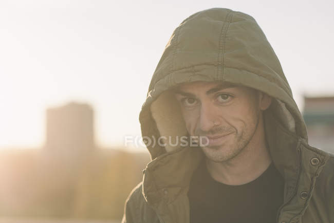 Portrait of smiling man wearing hooded jacket outdoors at sunset — Stock Photo