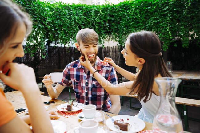 Счастливая молодая пара с другом сидят на улице, пьют кофе и торт — стоковое фото