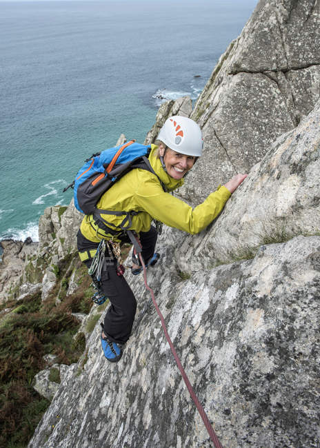 Royaume-Uni, Cornouailles, femme souriante grimpant sur Commando Ridge — Photo de stock