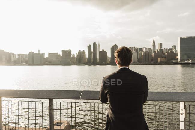 Hombre de negocios mirando el horizonte de Manhattan, Nueva York, Estados Unidos - foto de stock