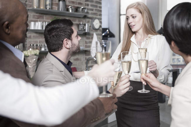 Друзья, держащие бокалы для шампанского и общающиеся на кухне — стоковое фото