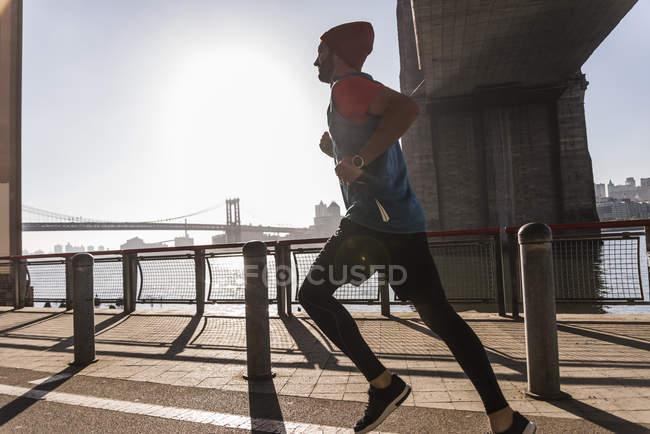 Соединенные Штаты Америки, New York City, Man running at East River — стоковое фото
