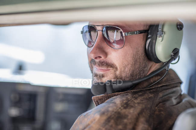 Portrait of Young pilot sitting in cockpit — Stock Photo