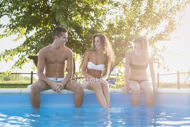 Drei Freunde entspannend am Beckenrand — Stockfoto