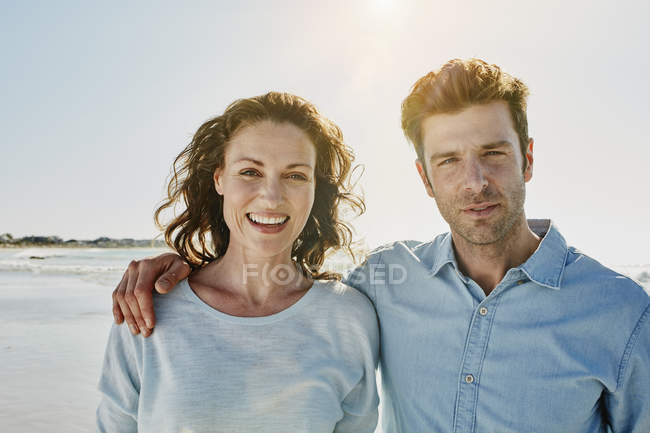 Portrait of smiling mid adult couple standing on beach — Stock Photo
