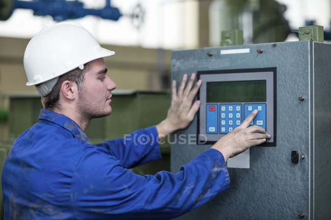 Worker operating machine in factory — Stock Photo