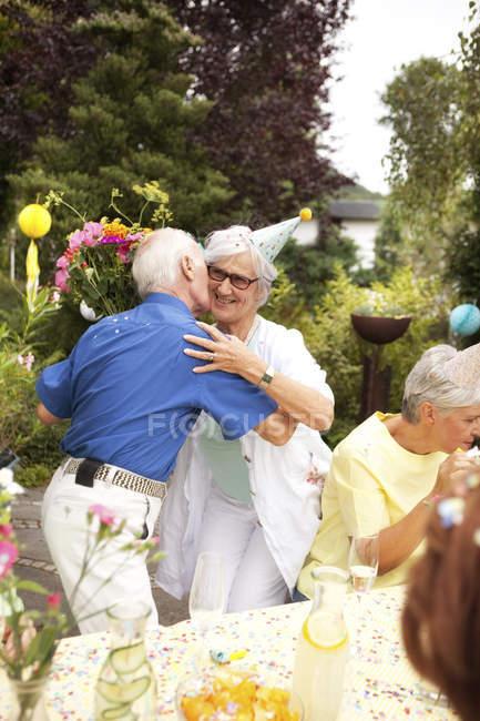 Senior man kissing elderly lady at birthday party — Stock Photo