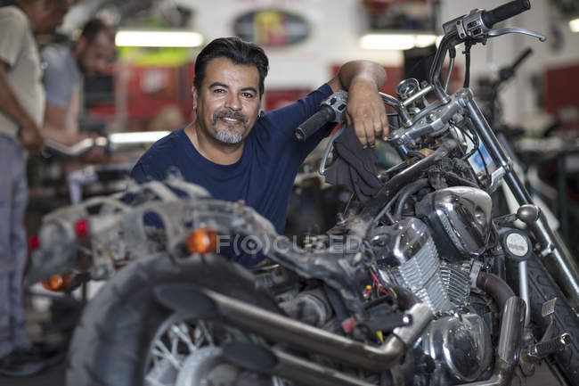 smiling motorcycle mechanic in workshop looking at camera stock photo