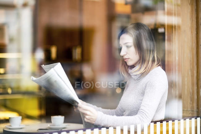Young woman sitting in coffee shop, reading newspaper — Stock Photo