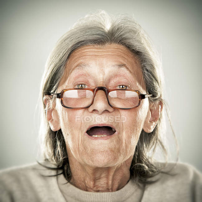 Portrait of senior woman with opened mouth looking at camera — Stock Photo