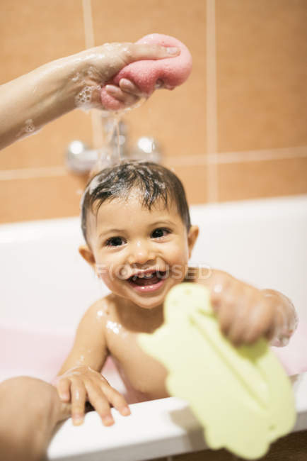 Portrait of happy toddler in bath tub getting washed by mother — Stock Photo