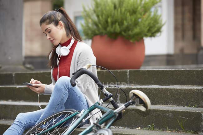 Femme avec casque et vélo assis sur les escaliers et utilisant un téléphone portable — Photo de stock