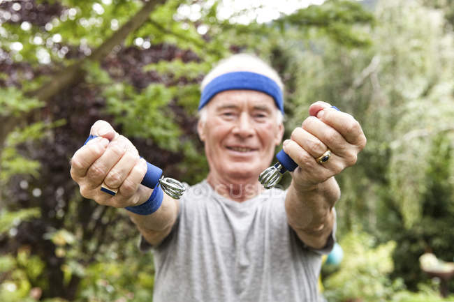 Senior man doing fitness training with gripper in his garden — Stock Photo