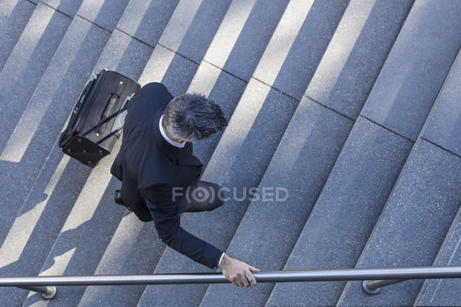 Businessman walking with suitcase on stairs — Stock Photo