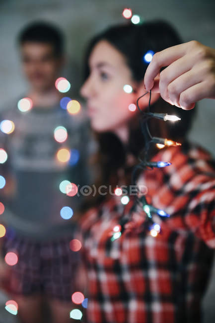 Hand of woman holding fairy lights — Stock Photo