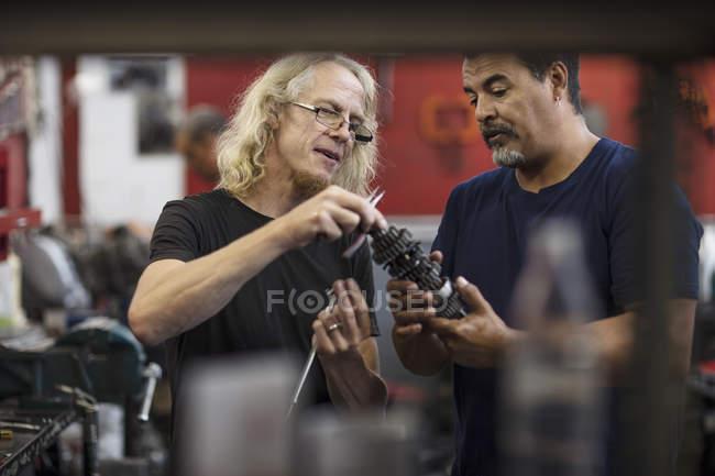 Zwei Mechaniker diskutieren Maschinenteil in Werkstatt — Stockfoto