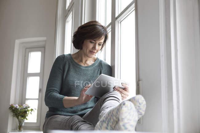 Frau benutzt Tablet, während sie zu Hause auf Fensterbank sitzt — Stockfoto