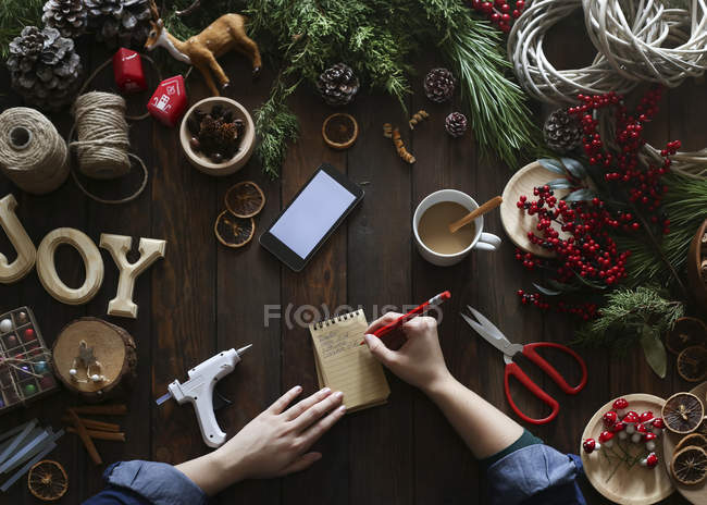 Woman's hands writing  on notepad at her desk at Advent — Stock Photo