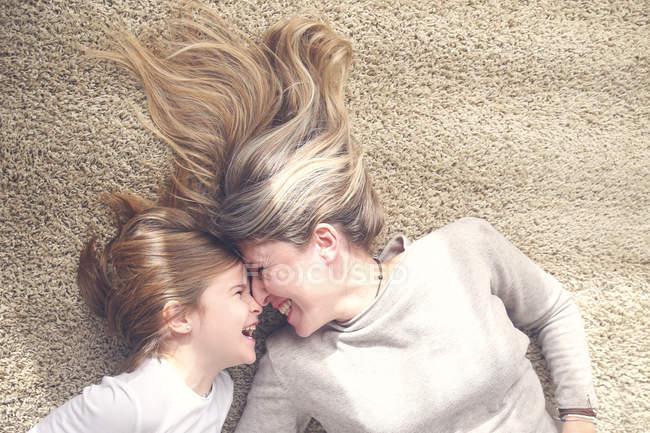 Мать и маленькая дочь лежат на ковре и веселятся — стоковое фото