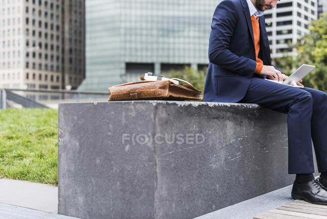 Бизнесмен работает открытый сидя на скамейке — стоковое фото