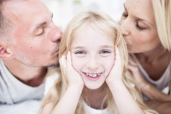 Portrait of smiling girl lying in bed with kissing parents — Stock Photo
