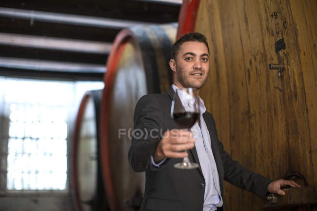 Young man testing red wine at wine estate — Stock Photo