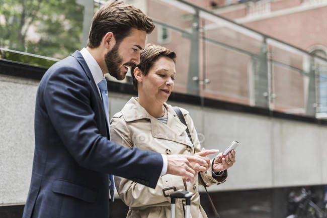 Smiling businessman and businesswoman sharing cell phone — Stock Photo