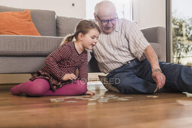 Grandfather and granddaughter playing memory on floor at home — Stock Photo