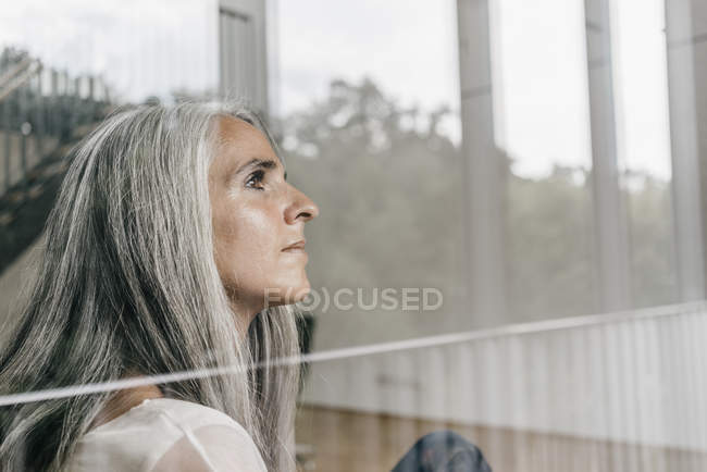 Woman with long grey hair looking out of window — Stock Photo