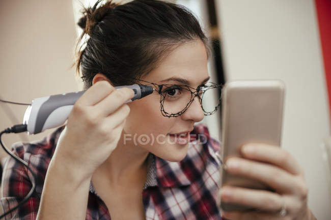 Young woman drawing with 3d pen on glasses — Stock Photo