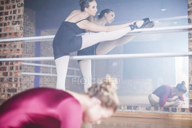 Ballet dancer stretching leg at studio — Stock Photo