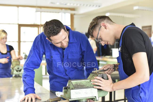 Ausbilder mit Auszubildender an der Werkbank — Stockfoto