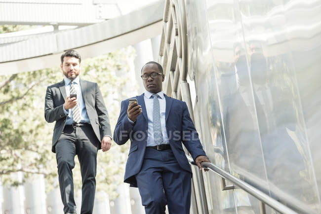 Two businessmen on the move using cell phones — Stock Photo