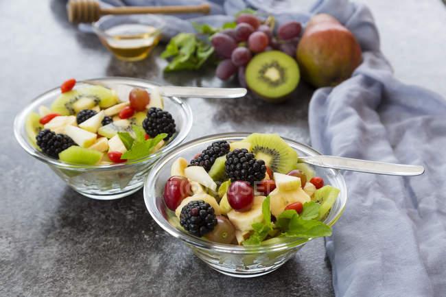 Salade de fruits aux mûres dans des bols à la surface grise — Photo de stock