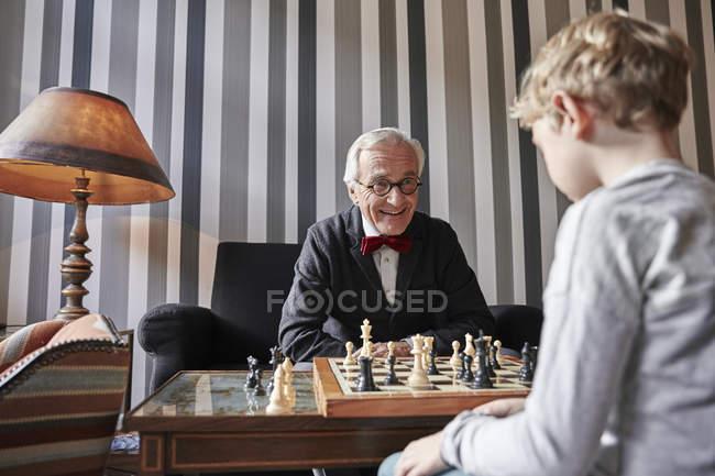 Abuelo y nieto jugando al ajedrez en la sala de estar - foto de stock